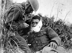 WW I: A soldier of Company K, 110th Regt. Infantry (formerly 3rd and 10th Inf., Pennsylvania National Guard), just wounded, receiving first-aid treatment from a comrade. Varennes-en-Argonne, France, on September 26, 1918. (U.S. Army/U.S. National Archives)