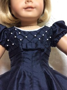 Beautiful dark navy Dupioni silk dress will take your doll in style to any special occasion. -High waisted bodice has diagonal tucks with hand sewn pearls at each intersection. The bodice has white piping at the neckline, a bias band all around, and a flat bow at center front.