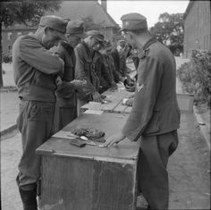 At the end of the World War II, the largest part of the German armed forces under western Allied control was immediately demobilized. Here, German soldiers at the British No.14 Disbandment Control Unit at Eutin barracks are handing in all military equipment, insignia, and paperwork. Each soldier received the amount of 40 marks to help him with returning home.