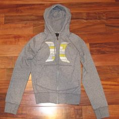 Hurley gray zip up Size small. Gray zip up hoodie with Hurley symbol on front in shades of white, gray and yellow. Shoulder to bottom of zip up measures 22 inches and arm length measures 29 inches. 80% cotton and 20% polyester. In great condition. Feel free to ask me any questions Hurley Tops Sweatshirts & Hoodies
