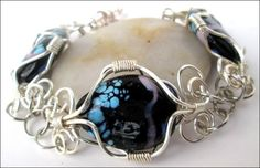 Hand Wire Wrapped Black, Purple, Blue, Lampwork Beaded Bracelet;  This handmade non-tarnish silver wire wrapped bracelet is a one of a kind bracelet.   The oval lampwork beads have a luscious deep ric