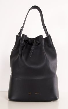 "Authentic Celine black leather Seau drawstring bucket handbag. Features gold-tone hardware, and adjustable flat leather top handle (10"" drop max.), four protective metal feet on bottom, and a top drawstring closure. Interior of handbag is lined in beige suede. Includes Celine dust bag, a tethered pochette, ans product care booklet. Made in Italy. Authenticity/Serial #: 9-PA-0191. Features Size: 9.5in x 13.75in x 6in Color: Black Material: Leather Handles: 10in drop Closure: Drawstring…"