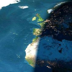This photograph was taken by the crew on board the Columbia during its last mission, on a cloudless day. The picture is of Europe and Africa when the sun is setting. Half of the picture is in night. The bright dots you see are the cities' lights. Note that the lights are already on in Holland, Paris, and Barcelona and that's it's still daylight in Dublin, London, Lisbon and Madrid