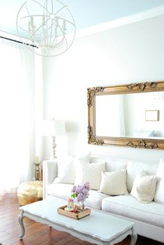 Love this all-white traditional living room with touches of gold in the forms of a Moroccan pouf, gilded table lamp, and carved baroque French mirror over the white linen sofa.