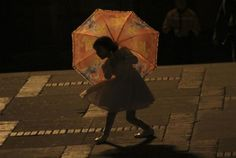 A girl plays with an umbrella during the closing ceremony of the XIII Ibero-American Theater Festival in Bogota, April 8, 2012.