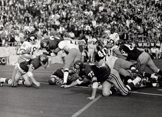 Black and white photo of an unidentified University of Oregon running back diving forward with the football as linemen collide during a game played in the early 1980s at Autzen Stadium. ©University of Oregon Libraries - Special Collections and University Archives