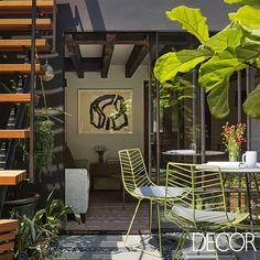 Cadeiras com design delicado e que se assemelham ao formato de uma folha entram em harmonia com o verde do entorno natural