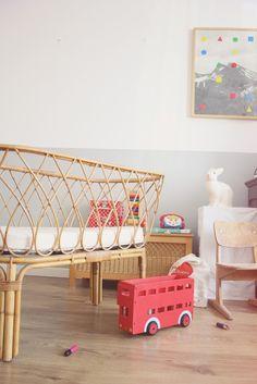 Kinderkamer met een half-om-half geschilderde muur. Het kleurige speelgoed zorgt voor contrast met de rustige kleuren. Let ook op de 'gevlochten' wieg. #kinderkamer #interieur #inspiratie