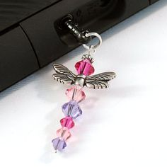 The dragonfly charm sparkles with fuchsia, rose pink and tanzanite as light hits and reflects from the Swarovski crystals. The dragonfly wings are two