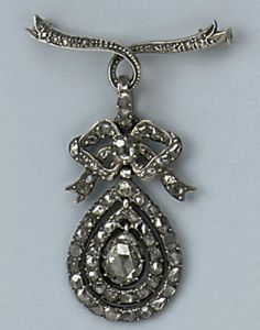 AN ANTIQUE ROSE-CUT DIAMOND PENDANT  Designed as a rose-cut diamond set ribbon bow supporting similarly set pear-shaped loops centering a larger stone, to a later brooch fitting and chain, pendant circa 1800.