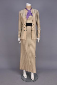 British wool walking suit, 1911-1913. Off-white with broken black stripe, sleeveless dress having cotton bodice, dotted net high neck insert and lilac silk tie over wool panel, black half cummerbund, long skirt with pleated back floating panels, jacket with shaped lapel and deep cuff with faux buttons, self belt, trimmed with black silk. B-38, W-30, H-38