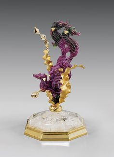 <b>RUBY SEAHORSE GROUP</b> <br  /> <i>Artist: Luis Alberto Quispe Aparicio</i> <br  /> A delightful grouping, these seven little seahorses are all carved from one single piece of rich purple ruby, delicately patterned in places with contrasting apple green zoisite. Each boasts fine bony skin detail, garnet eyes and gold pectoral fins, rising from between three floating golden tendrils of oceanic flora, atop a domed octagonal gold-banded quartz base, 7 3/8 inches high overall.