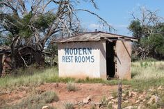 "Endee, NM - 2014 : This abandoned cabin with ""modern restrooms"" painted on the side, offers a unique photo opportunity."