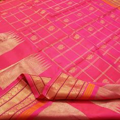 Borrowing its colour from vibrant tourmalines, this #silk sari in neon pink with gold checks will add to your heirloom collection. Gold peacock motifs dot alternate squares and the zari border is enhanced with tangerine, purple and large temple motifs. The pink pallu is a sea of gold with peacock and traditional motifs. Plain neon pink with running border completes this Sarangi #sari. An offering from Sarangi's pretty pinks. Code 580125601.