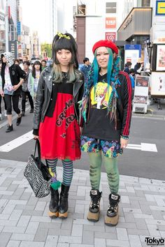 """Barbara (right) is wearing an Adidas """"TV Westfalia"""" jacket over a Kishidan t-shirt, Jammin shorts, moth print tights, and Buffalo platform boots. Accessories include a horn-and-tail beret, several eyeball rings from Goreglo, bracelets from Wataame, and a Jammin shoulder bag. Occhiy (left) is wearing a Sexy Dynamite London leather biker jacket over a Rodeo Crowns dress, striped tights, and classic Vivienne Westwood rocking horse shoes. Accessories include a Kishidan purse, and several rings."""