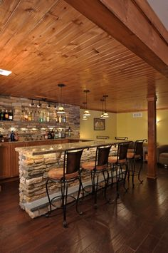 Now this home basement bar is impressive.  The design of the rock being recessed for the bottles is excellent.  First class.