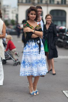 Miroslava Duma in white midi skirt w/ jay/sky floral print, sky/jay stilettos, black/green/red/gold fringe shawl