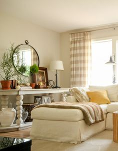Round mirror vignette, cream slipcovered sectional, horizontal striped drapes.