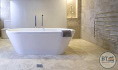 Large white oval bath set in the middle of the bathroom. Earthy tiles help to set off the clean white bath.