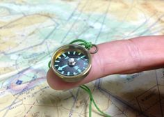 COMPASS, MAGNETIC -  These compact compasses are usually seen in Aircrew Survival Kits and seldom seen by the public. Overall Height: 0.213 inches; Overall Diameter: 0.075 inches;  Case Material: Machined Brass; Crystal Type: Acrylic; Instrument Type: DRY (will not freeze or develop bubbles); Diameter: 0.750 in; Din sealed brass case; threaded with 45 lb braided nylon fish line;  compass card has prominent luminous paint markings. From COUNTY COMM - $5.85 USD