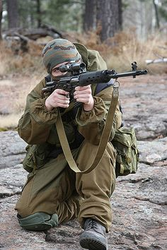 SVD sniper in use.This Russian sniper demonstrates the proper aiming position of the SVD. Note the support hand is holding the magazine and not the hand guards. The sling is allowed to hang free so it does not induce pressure on the barrel.  Photo by RomanS.