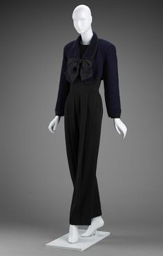 Woman's ensemble (jumpsuit and jacket) | Designed by Geoffrey Beene (American, 1927-2004) | United States, 1990's | Wool knit; wool plain weave (boucle); silk grosgrain ribbon | Black long sleeve jumpsuit. Navy wool bolero jacket with long sleeves and a black grosgrain ribbon bow at the collar | Museum of Fine Arts, Boston