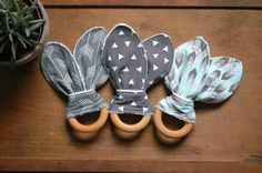 Your choice of 1 or 3 bunny ear teethers in modern shades of grey and pale blue, including geo triangles, arrows, and a feathered herringbone print. All 3 are backed with 100% cotton terry cloth, great for soaking and chilling in the freezer as an added comfort for aching gums (dont freeze the wood, please). These ears are great for baby to hold onto and help him/her keep the hardwood, maple wood ring in her chompers. These can be tied and knotted or lopped and secured as shown. A great…