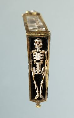 A sixteenth-century French gold, enamel and rock-crystal in the form of a coffin enamelled in black and white, with a hinged rock-crystal cover, containing a skeleton in high relief; the reverse and inside are enamelled with tongues of fire. (British Museum)