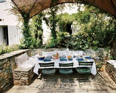 En Plein Air - Inspired by a pergola seen chez Marella Agnelli, a split-reed structure covered in jasmine and wisteria shades the designers' alfresco dining space.