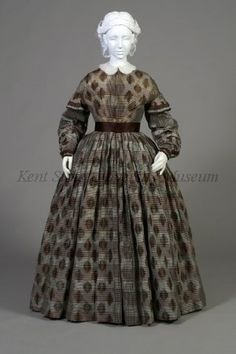 1840-1849Brown, beige, black dress of woven silk ikat, stripes and ikat checks. High neck, fastens front to waist, full skirt, dropped shoulder, ruffle at upper arm sleeve shaped with fullness at elbow, narrow cuff, trimmed with brown and plaid ribbon on outside edge