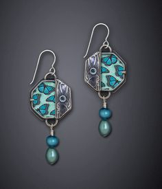 Blue Monarch Earrings by Dawn Estrin. Cast and hand-fabricated sterling silver earrings accented with Swarovski crystal, freshwater pearl, black onyx and featuring color photo-montage printed on archival paper and protected with a beveled scratch resistant polycarbonate plastic.