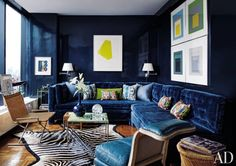 Lacquered walls and a custom-made St. Thomas–style sofa upholstered in a Lee Jofa velvet set a glamorous tone in the living area of Todd Alexander Romano's New York City pied-à-terre. A Ward Bennett wicker Sled chair and prints by Robert Goodnough and Josef Albers provide lively counterpoints.