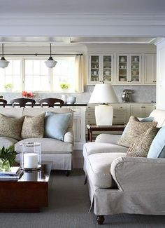 Hamptons style-cozy sofas and bright, open kitchen.