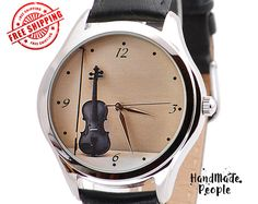 Elegant Ladies Watch With Beautiful Violin Photo on Beige Background.  Watch Case Plating Color: Golden (IP Plating) Type: Womens Watches Watch face Diameter: 3,8 cm approx. 1,5 inches Occasion: Gifts for Musicians, Music Teacher Gift, College Graduation Gifts, Birthday Gifts Movement: Japanese quartz movement (Miyota) Band Material: Two-sided Leather Water Resistant: 3 ATM or 30 m (Suitable for everyday use. Splash/rain resistant. NOT suitable for showering, bathing, swimming, snorkelling…