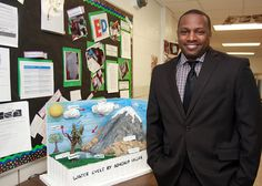 Staff / Katherine Frye / Principal Oliver Lewis displays a water cycle project created by a fourth-grade student in the STEM program.