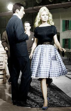 Brigitte Bardot in a gingham print skirt, black top, and flats