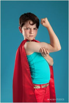 boy making muscle wearing superman costume for photo shoot at Boggio Studios