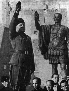Mussolini giving the fascist salute and a statue of Julius Cesar