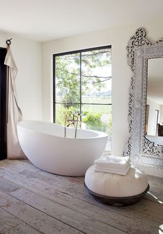 loving this luxe bathroom - the contemporary tub and traditional mirror are a…