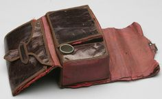 """Nineteenth Century glazed leather sewing kit. 1860s. Brown leather and lighter brown fabric binding, red silk lining, brass lock still works, Simon Bros Co. metal thimble (not original); 3 compartments, original silk covered pincushion on one side; width: 4.5""""; height: 3""""; depth: 2""""."""