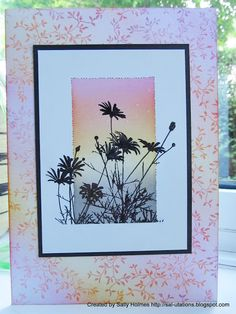 "By Sally Holmes. Card front stamped with Inkylicious ""Delicate Vines"" probably using VersaMark. She used pink and yellow inks on ink dusters (aka color dusters) to cover the card front. You could sponge. Main image: Use glossy cardstock. Mask to leave a rectangle open & sponge/use dusters to make background sunset (pink yellow, slate inks). Stamp flowers in black dye ink. Stamp is Inkylicious ""Daisy Fields."""
