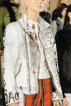 Graffiti white painted leather jacket (specially made for the presentation)T-shirt 'Prism'Trousers 'Be'She is punk!Class of 2002–2003Jurgi Persoons, Fall–Winter 2002–2003Photography by Ronald Stoops | Graphic Design by Chika Ujihara