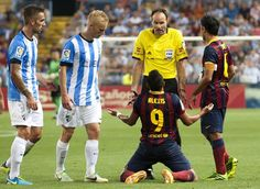 F.C. Barcelona's Alexis Sanchez, from Chile, center, reacts in front of the referee during a Spanish La Liga soccer match against Malaga at La Rosaleda stadium in Malaga, Spain, Sunday, Aug. 25, 2013