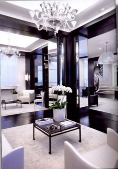 Modern. Gorgeous dark wood flooring with plush white area rugs, white leather chairs, mirrors, chandeliers, and winding staircase.