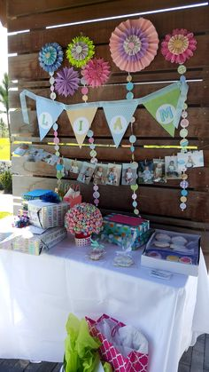 whimsical gift table for spring candy themed children's party with pennant banner, pinwheel flowers, paper circle garland, lollipop topiary, individually wrapped candy and cupcake themed cookies, with baby's first 12 months picture display on twine with clothespins.