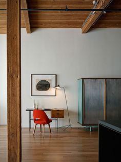 Hier maken de rode designstoel en de turkooise zij- en onderkant van de kast tegen de achtergrond van de witte wand en het houten plafond, de vloer en de balken het verschil: dit complementaircontrast zorgt voor een spannende maar subtiele kleurcontrastharmonie.