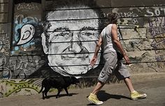 A man with his dog walk past a mural depicting actor Robin Williams in downtown Belgrade on August 13, 2014. Unknown artists drew the Academy Award-winning actor and comedian below a Belgrade bridge to pay a tribute following the news that he had been found dead of an apparent suicide at the age of 63.
