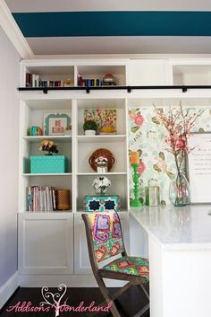 Built-in bookcases, a custom desk, teal striped ceiling and rolling library ladder create the ultimate home office space!