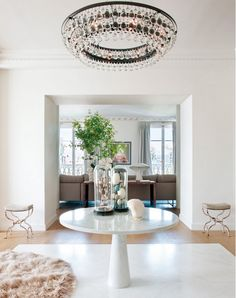 Neutral, grand entryway with marble Mangiarotti table.