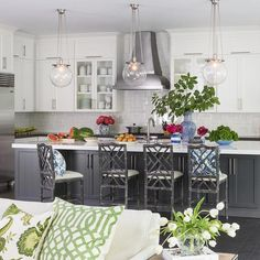 Three Rejuvenation Classic Globe Pendants illuminates a dark gray kitchen island topped with glossy white quartz fitted with a sink and a satin nickel gooseneck faucet lined with dark gray bamboo counter stools.